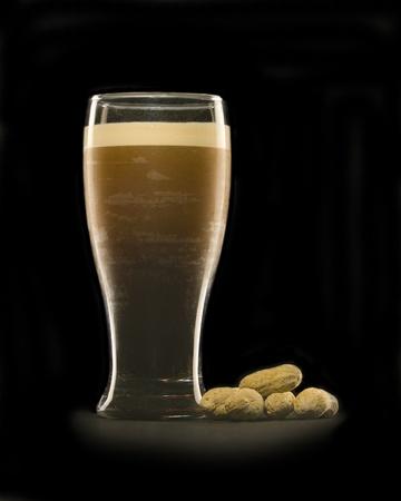 cerveza negra: La cerveza Stout, con la cabeza en unos frutos secos y el suelo de cristal en el lado