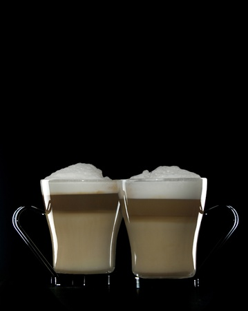 Two Cappuccino in clear mugs on black background