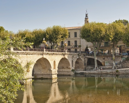 A bridge crosses a river to the city gate of the Medieval Village of Sommiers France