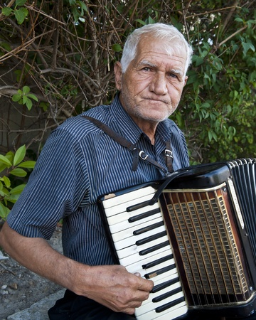 Old Man with wrinkled face plays old accordian with cracked keys in the medieval city of Avignon France for tips  Stock Photo