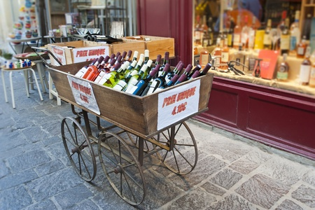 A cart of wine for sale in front of a wine and liquor shop in Uzes France Stock Photo - 13424289