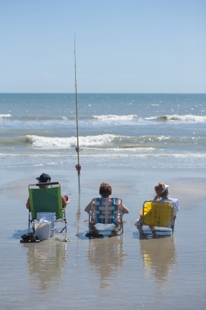 Three people surf fishing with one fishing pole at Cocoa Beach Florida