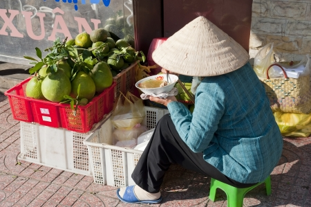 Vendor eating meal near Ben Thanh Market in Ho Chi Minh City