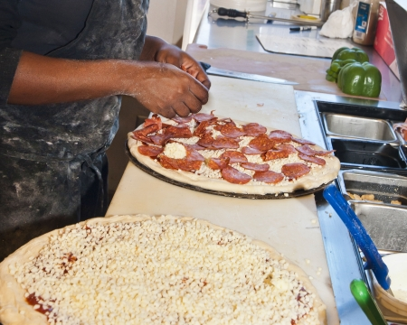 Putting Toppings on Pizza at a small business restaurant in Florida