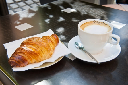 a breakfast of Croissant   Cappuccino at a sidewalk restaurant in France