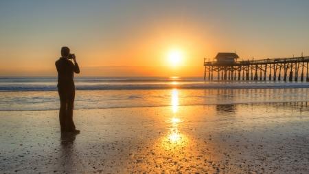 vrouw fotografeert Cocoa Beach Pier en zonsopgang Stockfoto