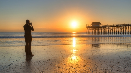 docks: woman photographing cocoa beach pier and sunrise