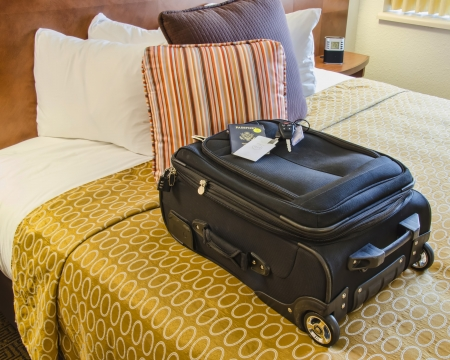 Roll Aboard Bag on a Hotel Bed with passport and car keys