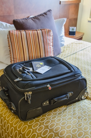 aboard: Roll Aboard Bag on a Hotel Bed Stock Photo