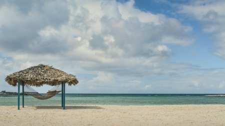 hammock and tiki hut on beach in Bahamas