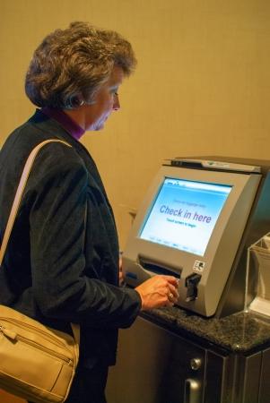 boarding card: Donna che usa chiosco per il check-in per il volo Archivio Fotografico