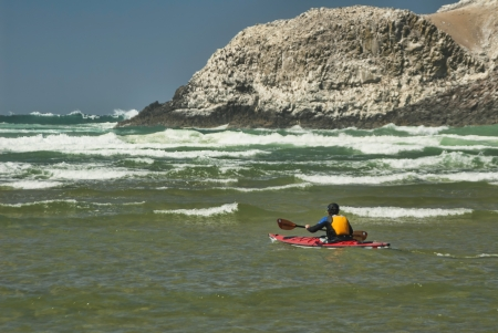 outbound: Kayaker paddling in Surf at Cannon Beach Oregon Stock Photo