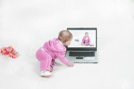 baby looking at own portrait