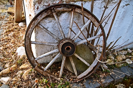 The old wooden wheel on a hay Stock Photo