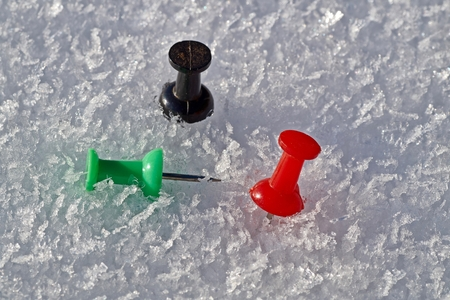Thumbtack in the colors red, black and green isolated on a snow background.