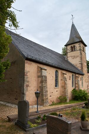 Church of St. Peter in Roth an der Our, Germany - a former church of the Knights Templar, partial summer exterior view under dramatic overcast sky Stock Photo