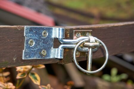 a slide latch on a wooden door photographed.
