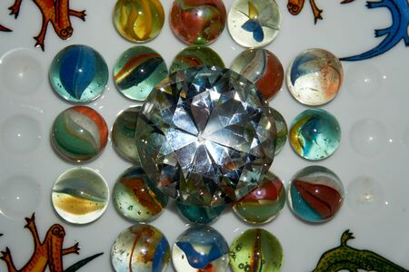 Yellow, green, blue and red glass marbles on a table