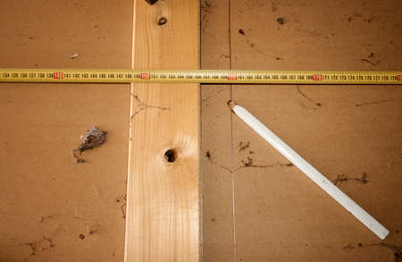 A wooden plate with various tools, pencil, measuring tape