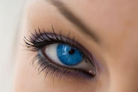 dilate: beautiful woman`s open blue eye