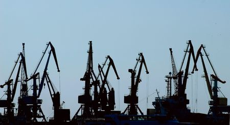 Silhouettes of hoisting cranes in harbor Standard-Bild