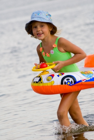 playing in the sea: Little sweet girl with inflatable swimming toy