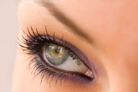 dilate: beautiful woman`s open green eye