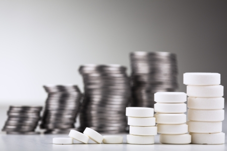 aspirin: Pile of white pills  in the form of a staircase  against pile of coins