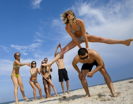 friends party: Young girl to jump across her boyfriend against joyful team of friends having fun at the beach  Stock Photo