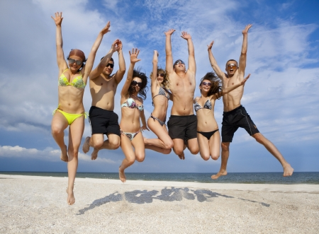 Joyful team of friends having fun at the beach  Standard-Bild