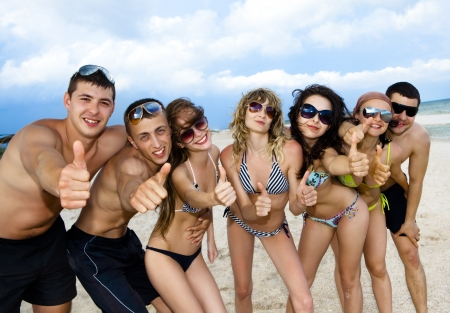 weekend activity: Joyful team of friends having fun at the beach and showing okay sign   Stock Photo