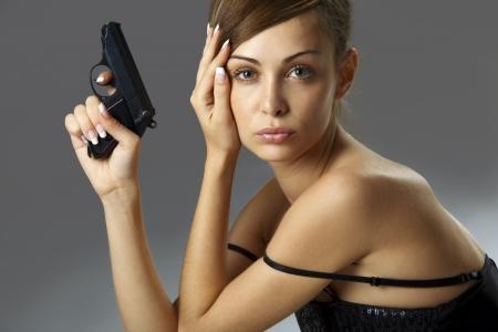 mujer con pistola: Atractiva mujer joven con arma de fuego sobre gris