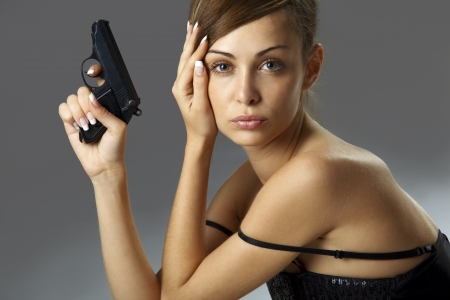 Attractive young woman with handgun over gray  photo