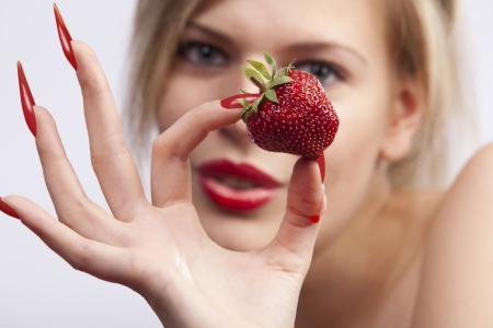 Sexy women with long red nails holding single strawberry  photo