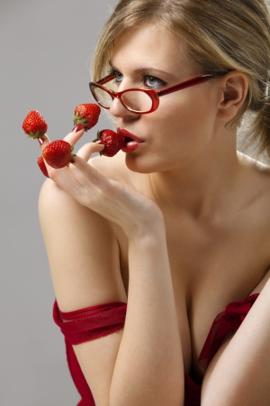Sexy young woman with red strawberries picked on fingertips isolated on gray background  photo