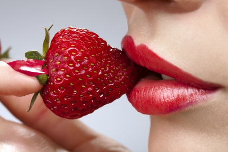Sexy young woman`s mouth with red strawberry picked on fingertips isolated on gray background  photo