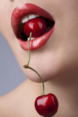 Young woman's mouth with red cherries  Standard-Bild