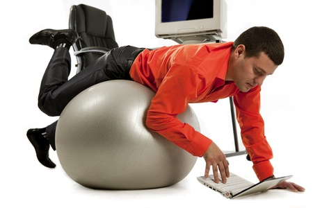 attractive office: Young businessman doing push-ups and looking on laptop screen  Stock Photo