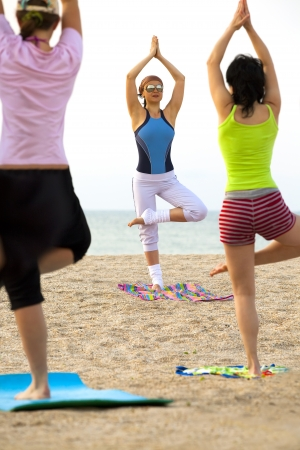 Young women doing fitness exercise on a beach  photo