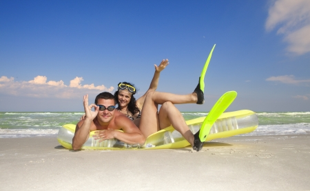 Romantic couple enjoying on an inflatable beach mattress