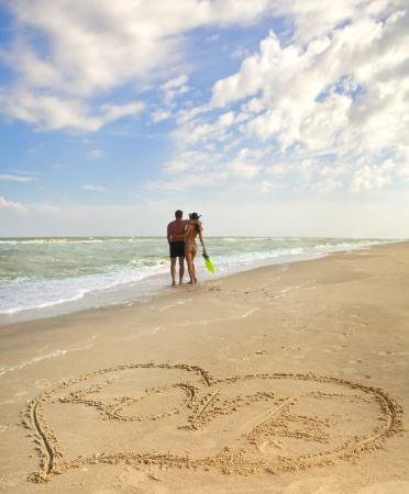 evoking: Hearts drawn on the sand of a beach (foreground), the man and woman on the background