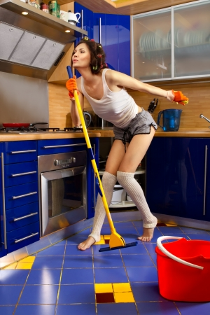 Smiling young woman cleaning the floor at home and singing photo