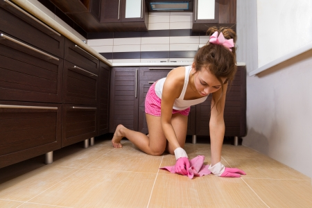 charwoman: Young woman cleaning the kitchen floor at home