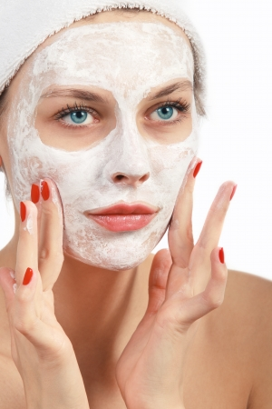 Beautiful young woman in towel doing cosmetic mask on her face Standard-Bild