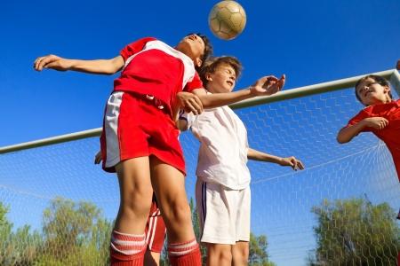 Chłopcy grający w piłkę nożną na boisku obok bramki Zdjęcie Seryjne