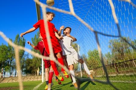 jugando al futbol: Los ni�os que juegan al f�tbol en el campo de deportes al lado de meta