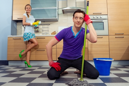 domination: Young man cleaning floor with his girlfriend at kitchen