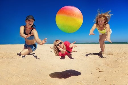 beach ball girl: Group of young joyful girls playing volleyball on the beach Stock Photo