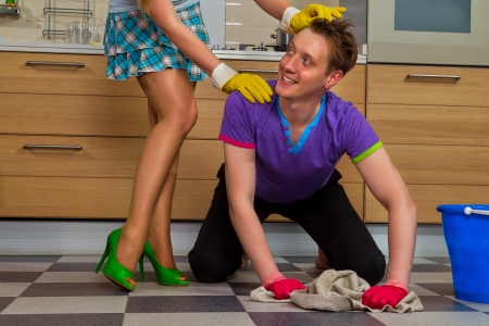 domination: Young man cleaning floor and looking at her girlfriend Stock Photo