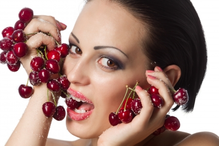 Beautiful young woman holding a bunch of red cherries covered with sugar photo